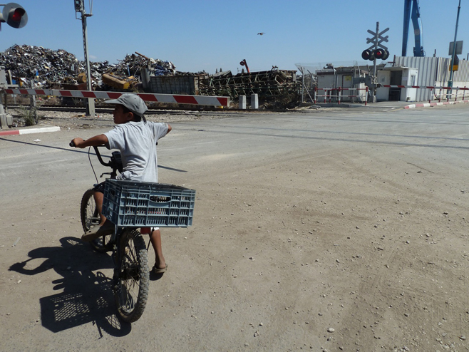 طفل من دهمش على وشك عبور قضبان القطار في طريقه إلى الطريق المؤدي لمدينة الرملة المجاورة
