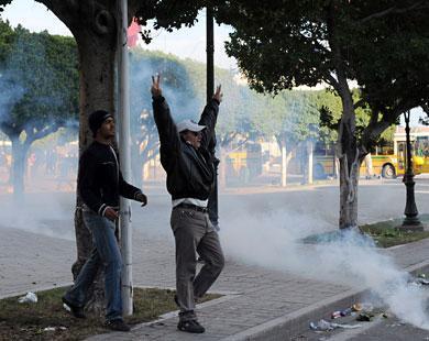 متظاهران غير عابئين بالقنابل المدمعة