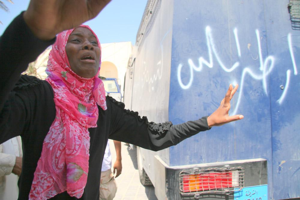 سيدة تقف أمام ملعب كرة باب البحر تطلب معلومات عن زوجها المحتجز