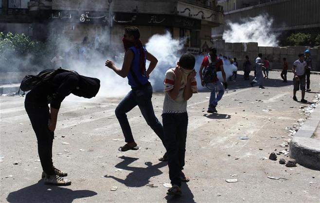 المتظاهرون يغطون وجوههم بعد أن أطلقت الشرطة الغاز المسيل للدموع أثناء مظاهرة قريبة من السفارة الأمريكية بالقاهرة، في 14 سبتمبر/أيلول 2012. © 2012 Reuters